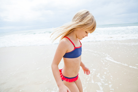 Happy cute young girl standing in water at beach on sunny day photo
