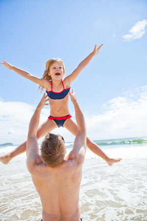 Father throwing happy smiling young daughter in air at beach with water and sky in background photo