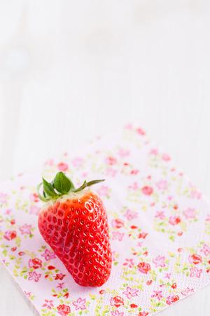 servilleta de papel: Primer plano de una fresa fresca que descansa sobre servilleta decorativa floral Foto de archivo