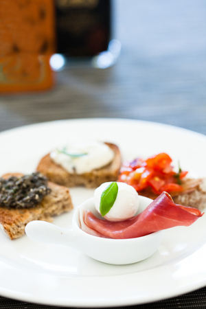 Closeup of plate of appetizers with prosciutto ham and mozzarella cheese and tomato and small pieces of dry bread photo