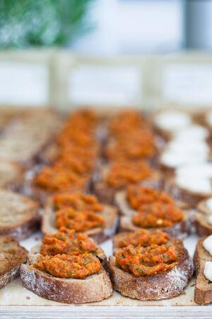 savoury: Крупным планом брускетта закусок с пикантным пасты долива представлены в строках