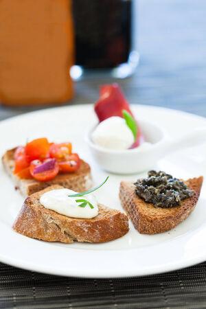 savoury: Крупным планом брускетта закусок с помидорами и солеными пасты и сыра моцарелла начинки на белой тарелке