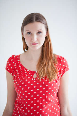 spotty: Studio portrait of thoughtful looking attractive woman wearing red spotty blouse Stock Photo