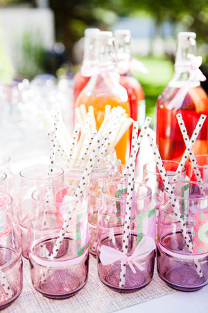 Closeup of decorative pink colored party glasses with straws on table outdoors with bottle of fruit juice in background Фото со стока