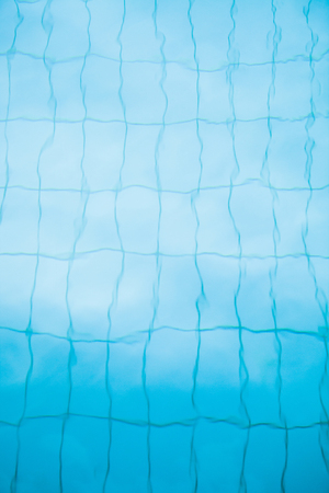 Tiles on bottom of swimming pool distorted slightly by water for background image photo