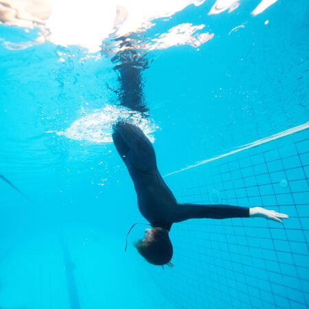 downwards: Female diver calmly diving downwards through surface into swimming pool Stock Photo