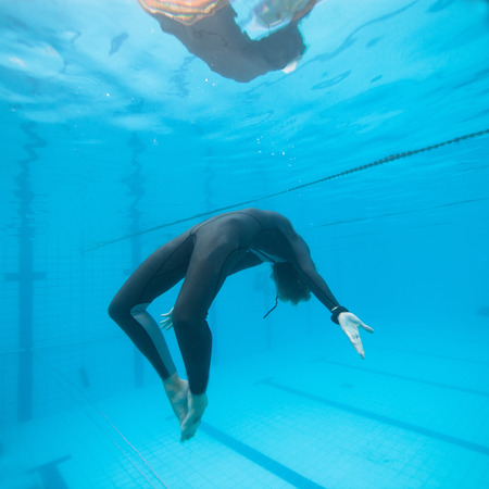 Woman freediving underwater in a pool photo