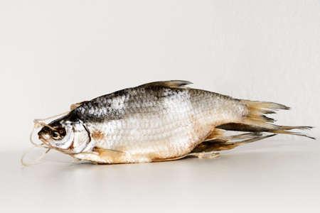 Pescado seco sobre la mesa. pescado salado seco de un río sobre un fondo blanco. pescado salado seco muertos - aperitivo a la cerveza. Aislado en blanco. . Foto de archivo