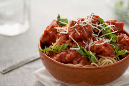 spaghetti pasta with Italian sausge in red bowl topped with Parmesan cheese and fresh basil Stock Photo