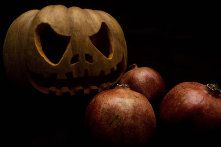 halloween pumpkin and pomegranates in a black background Фото со стока