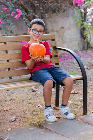 a child holding a pumpkin in the hand