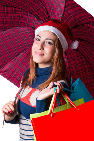a young natural woman with umbrella and bags. christmas hat Фото со стока