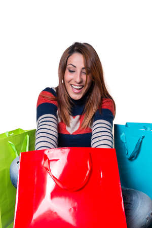 a natural happy young woman opening shopping bags
