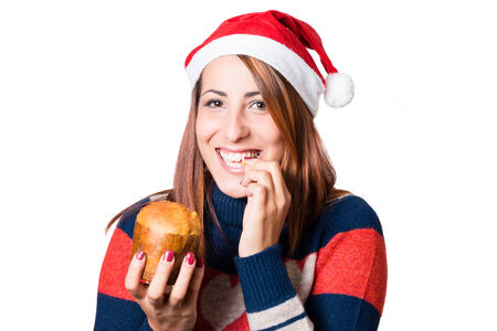 beautiful young woman with santa claus hat tasting a tipical italian christmas cake: Panettone.  Smiling, amused, in white background.