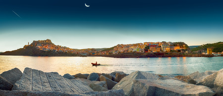 Castelsardo is a town in Sardinia, Italy, located in the northwest of the island at the east end of the Gulf of Asinara. Overview of the city at dawn, a boat crosses the gulf. city lights still on, the moon and a falling star.