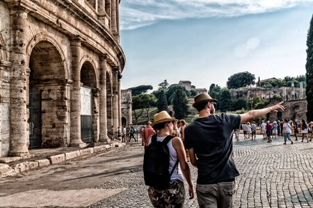 a couple of tourists visit the Coliseum, both with his hat, he points to the right, a lot of tourists in the background, clear sky and coliseum on the left
