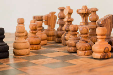handmade wooden chess board, two pawns face off Фото со стока