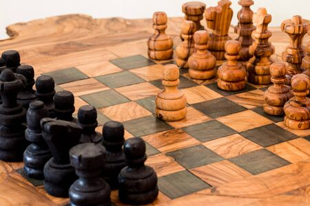 first move: handmade wooden chess board, pawn makes the first move
