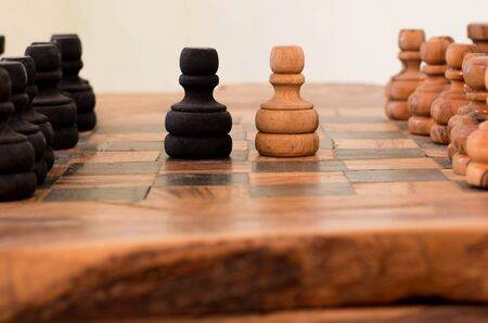 face off: handmade wooden chess board, two pawns face off Stock Photo