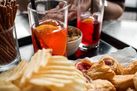 Tray ready for the appetizer, chips blurry in the foreground, drinks, snacks and pizzas in focus. an open hand in the background, glasses, straws, ice and orange.
