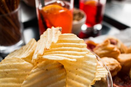 lose-up of a typical drink at the bar. Italian style. chips in the foreground, the background soft drinks and snacks all in glasses. Фото со стока