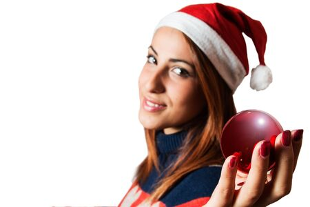 A natural girl holding a red Christmas ball, a Christmas cap, smiling, red fingernails, in golf turtleneck, isolated on white background, focus on balls, the girl slightly blurred.
