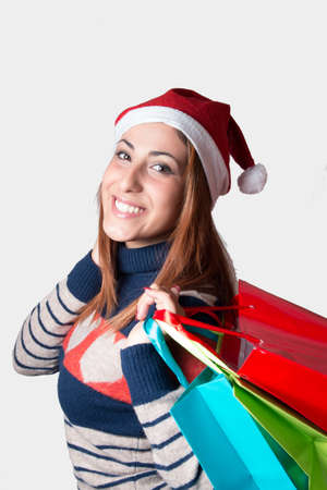 Young girl with christmas hat, shopping bags, smile, isolated.