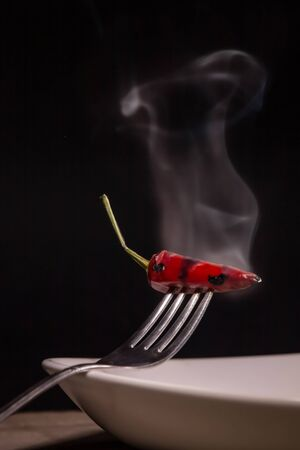 a steaming chili held by a fork, clouds of smoke remind the fire of spicy Фото со стока