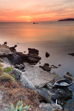 sunset on the rocks of Sardinia, a boat in the foreground, the background Capocaccia
