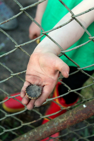 Rusty and rusty metal cap of the bottle is held by a childs hand by the superior metal mesh.