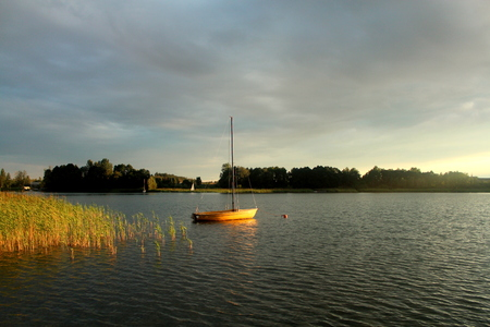 View of the boats on the lake Powidzkie in Poland during a summer sunset.