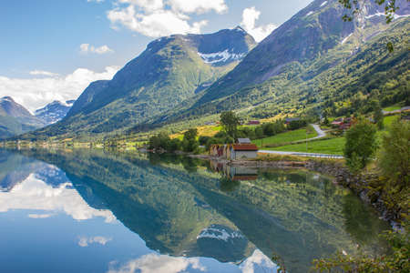 fiord: Scenic Norway with mountain backdrop reflecting in the fjord water Stock Photo