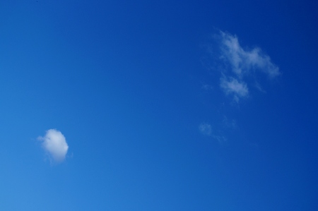 Two small clouds lost in the blue sky Stock Photo