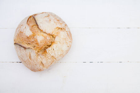 life loaf: Loaf of bread on a white wood table