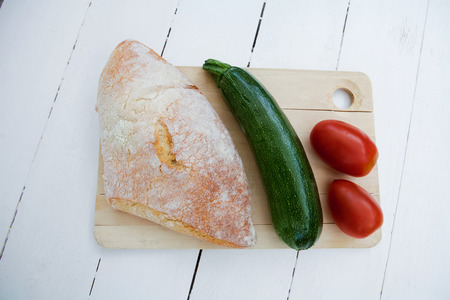 life loaf: Bread with zucchini and tomatoes on a cutting board
