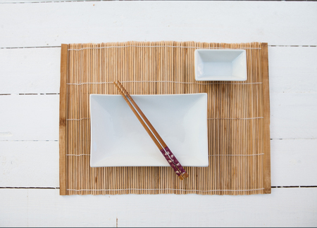 squared: Two white squared plates with chopsticks and a bamboo table cover on a white wooden table
