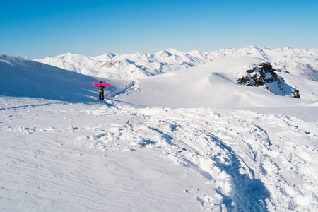 val: Snowboarder hiking on the snowy mountains in Val Thorens, France
