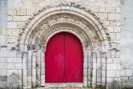 Very old red church door in Loire region, France