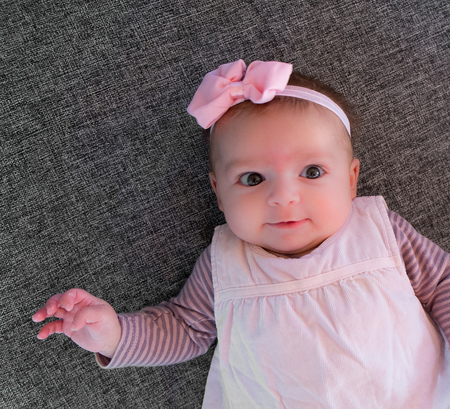Baby girl four month old with pink bow Standard-Bild