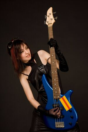 Beautiful girl playing bass guitar isolated in studio photo