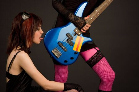 Two girls with bass guitar, one of them licking it photo