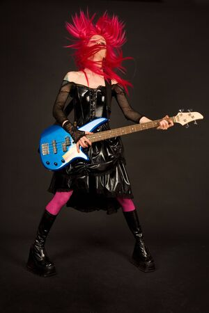 goth: Rock girl with bass guitar shaking her head