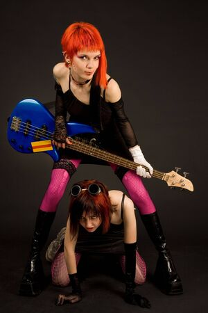 Rock girls with guitar isolated in studio photo