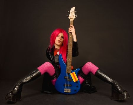 Attractive rock girl in crazy outfit sitting with bass guitar photo