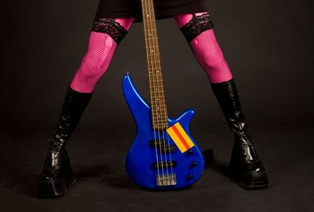 Close-up of woman legs with bass guitar isolated in studio photo