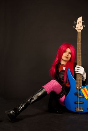 Rock girl in crazy outfit sitting with bass guitar photo