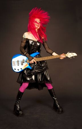 Rock girl with bass guitar shaking her head photo