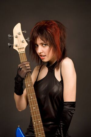 Beautiful girl with bass guitar isolated in studio photo