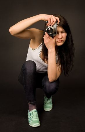 Young girl posing with old camera isolated on black background photo