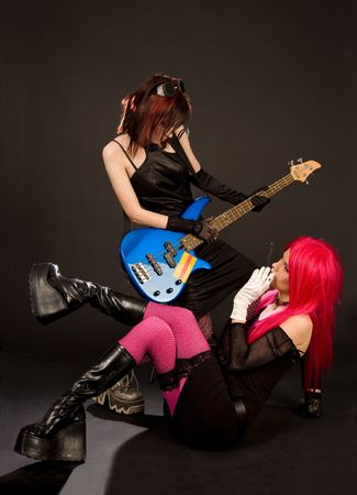 Two rock girls looking at each other isolated in studio photo